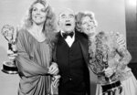 """FILE - In this Sept.17, 1978, file photo, Lindsay Wagner, left, Ed Asner, center, and Nancy Marchand pose at the 30th annual Primetime Emmy Awards at the Pasadena Civic Auditorium, in Pasadena, Calif. Asner won Outstanding Lead Actor in a Drama Series for """"Lou Grant."""" Marchand won Outstanding Continuing Performance for her supporting actress role in """"Lou Grant."""" Asner, the blustery but lovable Lou Grant in two successful television series, has died. He was 91. Asner's representative confirmed the death in an email Sunday, Aug. 29, 2021, to The Associated Press. (AP Photo, File)"""