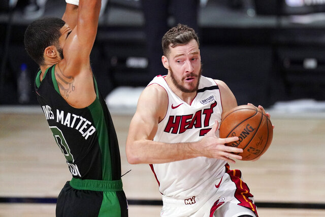 FILE - In this Sept. 25, 2020, file photo, Miami Heat's Goran Dragic (7) drives against Boston Celtics' Jayson Tatum (0) during the first half of an NBA conference final playoff basketball game in Lake Buena Vista, Fla. Dragic and Meyers Leonard have both decided to return to the Eastern Conference champions, each telling The Associated Press on Friday evening, Nov. 20, 2020, that they have agreed to accept Miami's offer of two-year deals -- the second year is a team option on both contracts -- to remain with the Heat. (AP Photo/Mark J. Terrill, File)