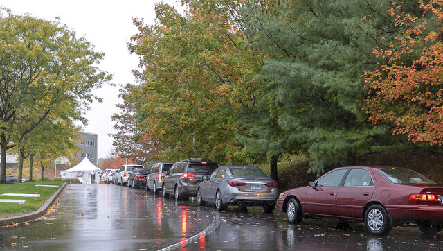 Cars line the COVID-19 drive through testing line at MidState Medical Center, Friday, Oct. 16, 2020 in Meriden, Conn. Hartford HealthCare, the parent company of MidState, has seen a recent spike in COVID-19 testing demand across all its properties, according to a Hartford HealthCare spokeswoman. (Dave Zajac/Record-Journal via AP)