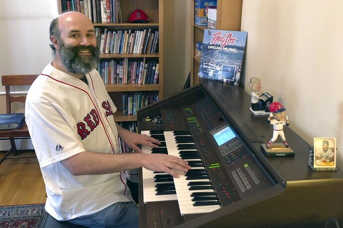In this April 2020, photo provided by Josh Kantor, the Boston Red Sox organist plays the organ in his home in Cambridge, Mass. Each afternoon since what would have been opening day, Kantor has been live-streaming concerts of ballpark music and other fan requests from his home in an attempt to recreate the community feeling baseball fans might be missing while the sport is shut down during the coronavirus pandemic. (Mary Eaton/Josh Kantor via AP)