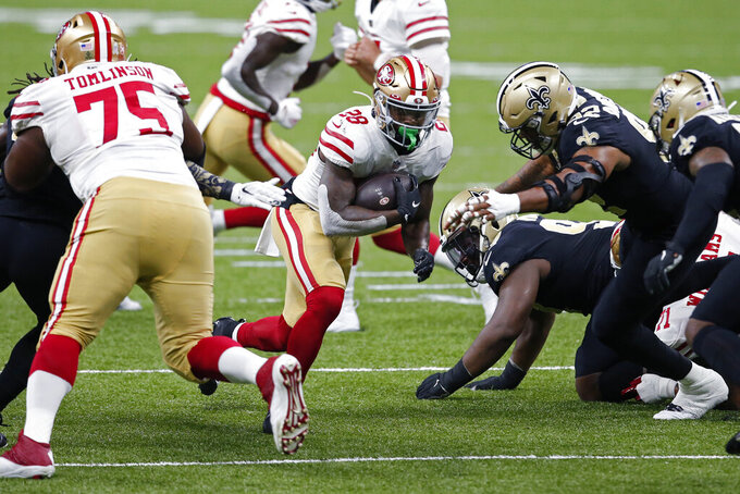 San Francisco 49ers running back Jerick McKinnon (28) carries through a hole as offensive guard Laken Tomlinson (75) blocks in the first half of an NFL football game against the New Orleans Saints in New Orleans, Sunday, Nov. 15, 2020. (AP Photo/Butch Dill)