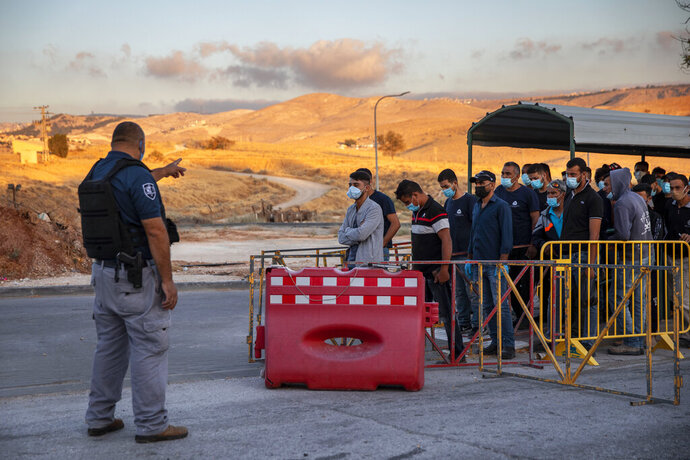 Palestinians laborers line up to cross a checkpoint at the entrance to the Israeli settlement of Maale Adumim, near Jerusalem, Tuesday, June 30, 2020. Israeli Prime Minister Benjamin Netanyahu appears determined to carry out his pledge to begin annexing parts of the occupied West Bank, possibly as soon as Wednesday. (AP Photo/Oded Balilty)