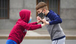 Boys play together while wearing face masks to protect against coronavirus infection, in St.Petersburg, Russia, Thursday, June 11, 2020. (AP Photo/Dmitri Lovetsky)
