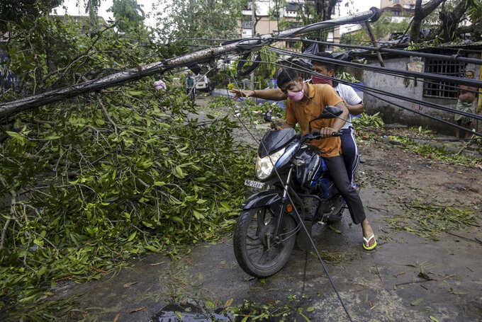 Motorists make their way through damaged cables and a tree branch fallen in the middle of a road after Cyclone Amphan hit the region in Kolkata, India, Thursday, May 21, 2020. People forgot about social distancing and crammed themselves into government shelters, minutes before Cyclone Amphan crashed in West Bengal. The cyclone killed dozens of people and the coronavirus nine in this region, one of India's poorer states. Even before the cyclone, its pandemic response was lagging; the state has one of the highest fatality rates from COVID-19 in India. With an economy crippled by India's eight-week lockdown, and health care systems sapped by the virus, authorities must tackle both COVID-19 and the cyclone's aftermath.(AP Photo/Bikas Das)