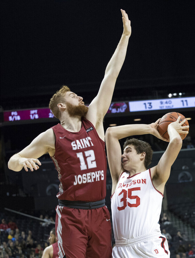 Saint Joseph's forward Anthony Longpre (12) defends as Davidson forward Luka Brajkovic (35) shoots during the first half of an NCAA college basketball game in the Atlantic 10 Conference tournament, Friday, March 15, 2019, in New York. (AP Photo/Mary Altaffer)
