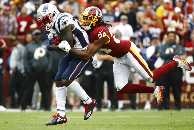 FILE - In this Oct. 6, 2019, file photo, Washington Redskins cornerback Josh Norman (24) tackles New England Patriots running back Sony Michel (26) during the second half of an NFL football game in Landover, Md. The Redskins have released Norman and wide receiver Paul Richardson. Norman struggled to live up to the $75 million, five-year contract he signed in 2016 after an All-Pro season in Carolina. He was let go with one year left on that deal. Norman's release and $12.5 million salary-cap savings could pave the way for Washington to give cornerback Quinton Dunbar a raise. Richardson's release doesn't save as much. (AP Photo/Patrick Semansky, File)