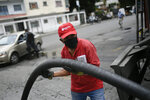 A worker wearing a face mask amid the new coronavirus pandemic works to fills up one of the tanks of a state oil company gas station in Caracas, Venezuela, Sunday, May 31, 2020. After decades of being the cheapest gasoline in the world, Venezuelan President Nicolas Maduro indicates that as of next Monday a new pricing scheme will be imposed on some 200 stations. (AP Photo/Matias Delacroix)