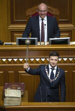 Ukrainian new President Volodymyr Zelenskiy holds a mace, the Ukrainian symbol of power, during his inauguration ceremony in Kiev, Ukraine, Monday, May 20, 2019. Ukrainian TV star Volodymyr Zelenskiy was sworn in as the country's new president on Monday, promised to stop the war in the country's east against Russian-backed separatists and immediately disbanded parliament, which he has branded as a group only interested in self-enrichment. Ukrainian parliament speaker Andriy Parubiy is in the background. (Markiv Mykhailo, Ukrainian Presidential Press Service via AP)