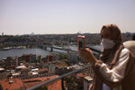 A woman takes photos, in Istanbul, Thursday, July 1, 2021. Turkey's government on Thursday eased restrictions in place to curb the spread of the coronavirus, and have reopened theaters, cinemas and other entertainment centers. (AP Photo/Emrah Gurel)