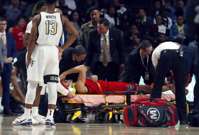 N.C. State's Jericole Hellems (4) is taken off the floor after being injured during the second half of an NCAA college basketball game in Winston-Salem, N.C., Saturday, Dec. 7, 2019. (Ethan Hyman/The News & Observer via AP)