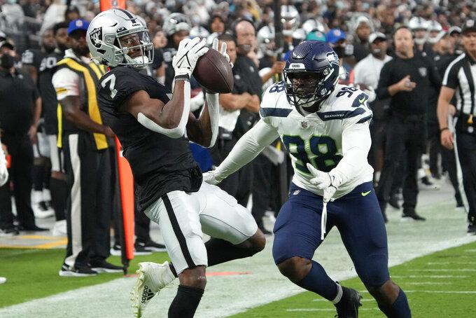 Las Vegas Raiders wide receiver Zay Jones (7) makes a catch against Seattle Seahawks defensive end Alton Robinson (98) during the first half of an NFL preseason football game, Saturday, Aug. 14, 2021, in Las Vegas. (AP Photo/Rick Scuteri)
