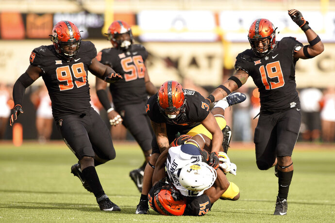 Oklahoma State defensive tackle Trey Carter (99) and offensive lineman Larry Williams (56) watch as teammates Kenneth Edison-McGruder (3), linebacker Justin Phillips (19) and safety Jarrick Bernard (24) stop the advance of West Virginia wide receiver Gary Jennings Jr during the first half of an NCAA college football game in Stillwater, Okla., Saturday, Nov. 17, 2018. Oklahoma State upset West Virginia 45-41. (AP Photo/Brody Schmidt)