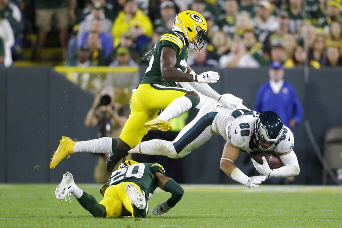 Philadelphia Eagles tight end Zach Ertz (86) is taken off his feet by Green Bay Packers cornerback Kevin King (20) after completing a catch during the second half of an NFL football game Thursday, Sept. 26, 2019, in Green Bay, Wis. (AP Photo/Jeffrey Phelps)
