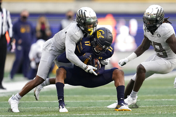 Oregon cornerback Mykael Wright, top, tackles California wide receiver Makai Polk (17) during the first half of an NCAA college football game in Berkeley, Calif., Saturday, Dec. 5, 2020. (AP Photo/Jeff Chiu)