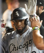 Chicago White Sox's Luis Robert is congratulated by teammates after hitting a solo home run off Cleveland Indians relief pitcher Trevor Stephan during the fifth inning of a baseball game in Cleveland, Friday, Sept. 24, 2021. (AP Photo/Phil Long)