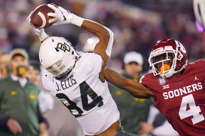 Baylor wide receiver Jaylen Ellis (84) catches a pass in front of Oklahoma cornerback Jaden Davis (4) in the first half of an NCAA college football game Saturday, Dec. 5, 2020, in Norman, Okla. (AP Photo/Sue Ogrocki)
