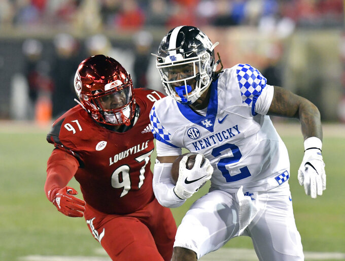 Kentucky wide receiver Dorian Baker (2) runs from Louisville linebacker Nick Okeke (97) during the second half of an NCAA college football game in Louisville, Ky., Saturday, Nov. 24, 2018. (AP Photo/Timothy D. Easley)