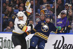 Buffalo Sabres defenseman Colin Miller (33) and Vegas Golden Knights forward Ryan Reaves (75) colllide behind the net during the second period of an NHL hockey game Tuesday, Jan. 14, 2020, in Buffalo, N.Y. (AP Photo/Jeffrey T. Barnes)