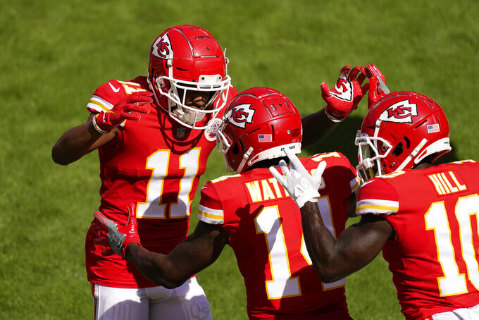Kansas City Chiefs wide receiver Sammy Watkins, center, celebrates with teammates Demarcus Robinson, left, and Tyreek Hill, right, after catching an 8-yard touchdown pass during the first half of an NFL football game against the Las Vegas Raiders, Sunday, Oct. 11, 2020, in Kansas City. (AP Photo/Charlie Riedel)