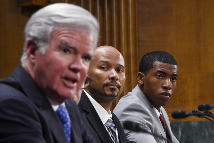 National Collegiate Athletic Association Student-Athlete Advisory Committee Chair Kendall Spencer, right, and National College Players Association Executive Director Ramogi Huma, center, listen as National Collegiate Athletic Association President Mark Emmert, left, testifies during a Senate Commerce subcommittee hearing on Capitol Hill in Washington, Tuesday, Feb. 11, 2020, on intercollegiate athlete compensation. (AP Photo/Susan Walsh)