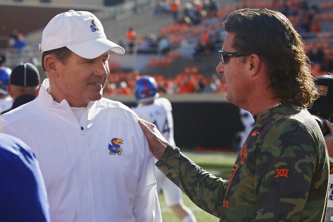 Kansas head coach Les Miles, left, talks with Oklahoma State head coach Mike Gundy, right, before an NCAA college football game in Stillwater, Okla., Saturday, Nov. 16, 2019. (AP Photo/Sue Ogrocki)