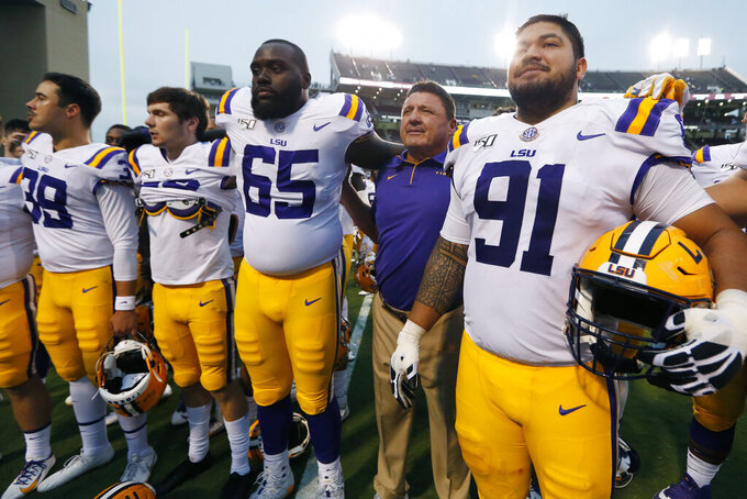 LSU head coach Ed Orgeron joins his players as they sing their school song following a 36-13 win over Mississippi State in an NCAA college football game in Starkville, Miss., Saturday, Oct. 19, 2019. (AP Photo/Rogelio V. Solis)