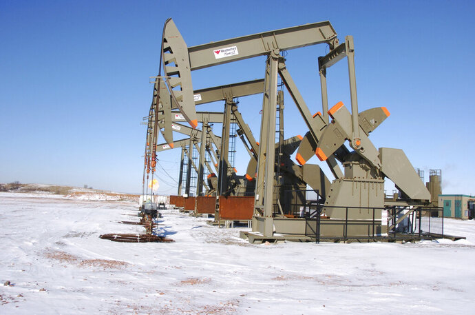FILE - This Feb. 26, 2015, file photo, shows an oil well on the Fort Berthold Indian Reservation near Mandaree, North Dakota. North Dakota Republican legislative leaders unveiled a bill Thursday, Jan. 17, 2019, that aims to stop a longstanding disagreement over shared revenues on the oil-rich American Indian reservation in the state. (AP Photo/Matthew Brown, File)