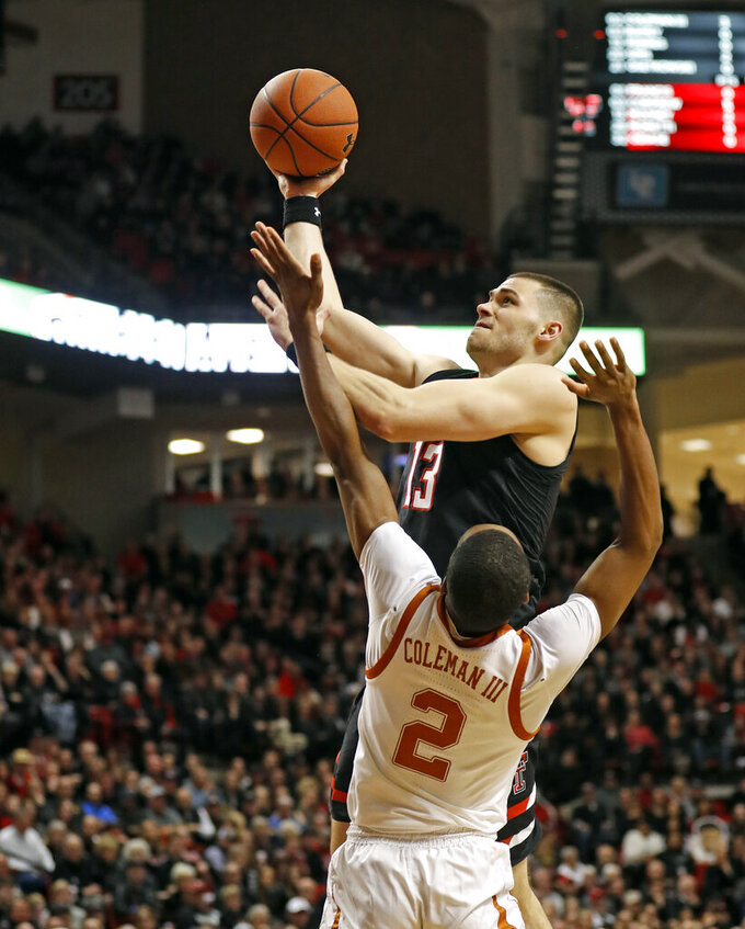 FILE - In this Monday, March 4, 2019, file photo, Texas Tech's Matt Mooney (13) shoots over Texas' Matt Coleman III (2) during the first half of an NCAA college basketball game in Lubbock, Texas. Eighth-ranked Texas Tech has been helped by two grad transfers, Mooney and Tariq Owens, in pursuit of the school's first Big 12 title after Elite Eight losses.  (AP Photo/Brad Tollefson, File)