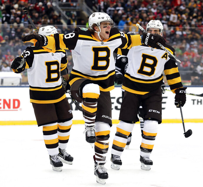Boston Bruins right wing David Pastrnak (88), center, celebrate after scoring his goal against the Chicago Blackhawks in the first period of the NHL Winter Classic hockey game at Notre Dame Stadium, Tuesday, Jan. 1, 2019, in South Bend, Ind. (AP Photo/Nam Y. Huh)
