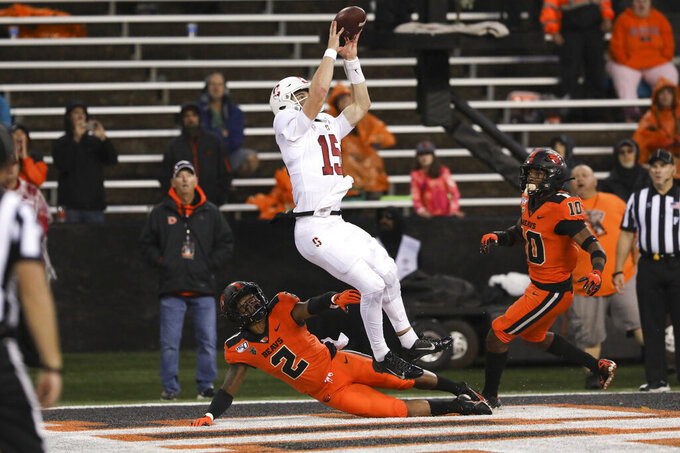 Stanford quarterback Davis Mills (15) dodges Oregon State defensive backs Shawn Wilson (2) and Omar Hicks-Onu (10) to catch an 8-yard pass from tight end Colby Parkinson (84) and score a touchdown during the second half of an NCAA college football game in Corvallis, Ore., Saturday, Sept. 28, 2019. (AP Photo/Amanda Loman)