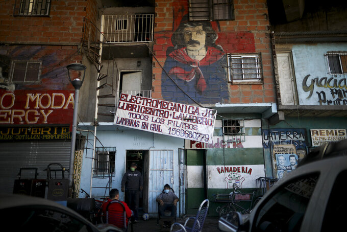 Residents, wearing protective face masks to help curb the spread of the new coronavirus, gather outside a shop in the Villa 31 slum during a government-ordered shutdown, in Buenos Aires, Argentina, Thursday, April 30, 2020. According to official data, the number of confirmed cases of COVID-19 in the city's slum have increased in the past week, putting authorities on high alert. (AP Photo/Natacha Pisarenko)
