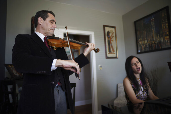 Musicians David Shenton and Erin Shields perform inside their home in the Queens borough of New York on March 30, 2021. The married couple have led virtual concerts from their living room to raise thousands of dollars for the Mosaic West Queens Church food pantry, where they volunteer every weekend. (AP Photo/Emily Leshner)