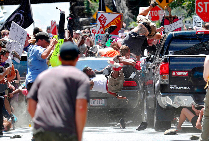 In this Aug. 12, 2017, photo by Ryan Kelly of The Daily Progress, people fly into the air as a car drives into a group of protesters demonstrating against a white nationalist rally in Charlottesville, Va. The photo won the 2018 Pulitzer Prize for Breaking News Photography, announced Monday, April 16, 2018, at Columbia University in New York. (Ryan Kelly/The Daily Progress via AP)