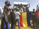 Mourners chanting with the coffin of one of the victims who was killed this week during his funeral at a cemetery in N'Djamena, Chad, Saturday, May 1, 2021.  Hundreds of chanting mourners carrying Chadian flags gathered Saturday to bury victims who were shot dead earlier this week amid demonstrations against the country's new military government.(AP Photo/Sunday Alamba)