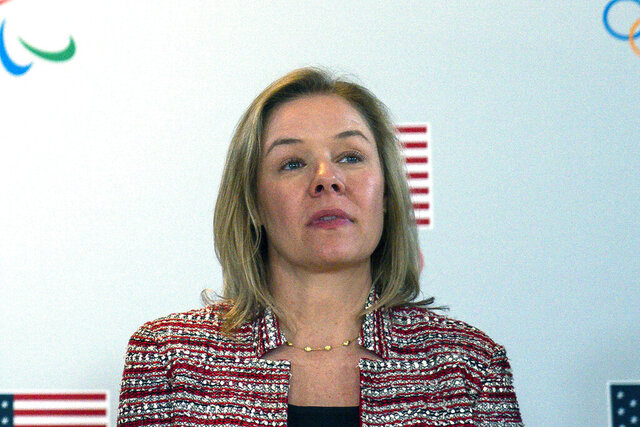FILE - In this Feb. 18, 2020, file photo, United States Olympic and Paralympic Committee CEO Sarah Hirshland listens as President Donald Trump speaks during a briefing with the U.S. Olympic and Paralympic Committee and Los Angeles 2028 organizers in Beverly Hills, Calif. Even before the coronavirus pandemic wiped the Summer Olympics off the 2020 sports calendar, the U.S. Olympic and Paralympic Committee was an organization in peril. In a first-of-its-kind virtual address, leaders of the committee paid heed to how much more difficult things have become since the virus started shutting down sports, over the last seven months. (AP Photo/Evan Vucci, File)