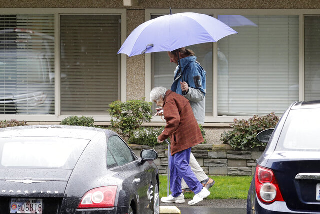 In this March 6, 2020 photo, Charlie Campbell, right, walks with his mother, Dorothy Campbell, to visit his father, Gene, who was staying at the time at the Life Care Center in Kirkland, Wash. Charlie Campbell is nearly 13 years sober, but said he has been feeling tested due to stress from having his father now recovering from the new coronavirus in a hospital, and several other sources of worry and stress in his life. (AP Photo/Ted S. Warren)