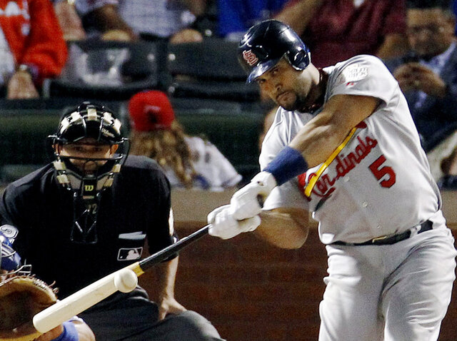 FILE - In this Oct. 22, 2011, file photo, St. Louis Cardinals' Albert Pujols hits a solo home run during the ninth inning of Game 3 of baseball's World Series against the Texas Rangers, in Arlington, Texas. Pujols was drafted in the 13th round in 1999. He was in the majors by 2001, when he won Rookie of the Year honors and drove in 130 runs. Three MVP awards later, Pujols is closing in on the end of his career — with 656 home runs and counting. (AP Photo/Eric Gay, File)