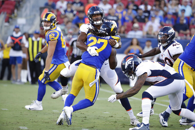 Los Angeles Rams running back Darrell Henderson (27) is tackled by Denver Broncos linebacker Justin Hollins during the first half of an NFL preseason football game Saturday, Aug. 24, 2019, in Los Angeles. (AP Photo/Rick Scuteri)