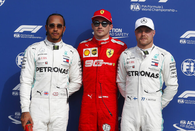 Ferrari driver Charles Leclerc of Monaco, who clocked the fastest time, poses between runner-up Mercedes driver Lewis Hamilton of Britain and third fastest Mercedes driver Valtteri Bottas of Finland, after the qualifying session at the Monza racetrack, in Monza, Italy, Saturday, Sept. 7, 2019. The Formula one race will be held on Sunday. (AP Photo/Antonio Calanni)