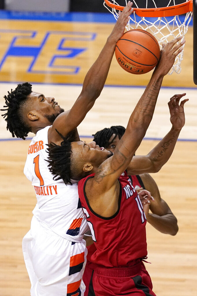 Syracuse forward Quincy Guerrier (1) battles North Carolina State forward Manny Bates (15)for a rebound during the first half of an NCAA college basketball game in the second round of the Atlantic Coast Conference tournament in Greensboro, N.C., Wednesday, March 10, 2021. (AP Photo/Gerry Broome)