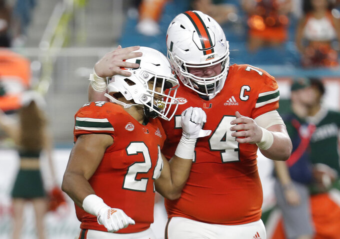Miami running back Travis Homer (24) is congratulated by offensive lineman Tyler Gauthier after scoring a touchdown during the second half of an NCAA college football game against Pittsburgh, Saturday, Nov. 24, 2018, in Miami Gardens, Fla. Miami won 24-3. (AP Photo/Lynne Sladky)