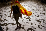FILE - In this Tuesday Oct. 3, 2017 file photo, a woman wearing an Estelada or independence flag, walks along a street covered with referendum ballots thown by pro-independence demonstrators, during a rally in Barcelona, Spain. Spain's Supreme Court is bracing to hold the nation's most sensitive trial in four decades of democracy this week with all eyes focused on its ability to stand up to concerted campaign by Catalonia's separatists to attack its credibility. (AP Photo/Emilio Morenatti, File)