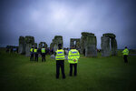 Police keep watch as people stand inside the stone circle during Summer Solstice at Stonehenge, where some people jumped over the fence to enter the stone-circle to watch the sun rise at dawn of the longest day of the year in the UK, in Amesbury, England, Monday June 21, 2021. The prehistoric monument of ancient stones have been officially closed for the celebrations due to the coronavirus lockdown, but groups of people ignored the lockdown to mark the Solstice, watched by low key security. (Ben Birchall/PA via AP)