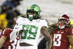 Oregon tight end DJ Johnson, center, carries the ball in front of Washington State linebacker Jahad Woods, right, and defensive back Ayden Hector during the second half of an NCAA college football game in Pullman, Wash., Saturday, Nov. 14, 2020. (AP Photo/Young Kwak)
