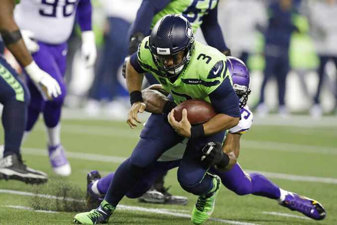 Seattle Seahawks quarterback Russell Wilson (3) is brought down by Minnesota Vikings' Danielle Hunter during the first half of an NFL football game, Monday, Dec. 2, 2019, in Seattle. (AP Photo/John Froschauer)