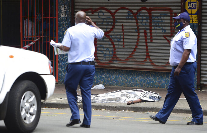 Police pass the lifeless body of a man allegedly shot dead during clashes with protesting students from the University of the Witwatersrand and police in Johannesburg, Wednesday, March 10, 2021.  At least one person has died and two students have been injured in clashes between South African university students and police over tuition fees at the University.  Protests erupted this week after thousands of students were denied registration for the 2021 academic year because they owed tuition fees from last year. (AP Photo)
