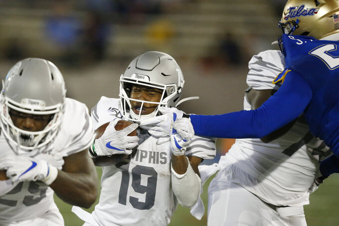Memphis running back Kenneth Gainwell (19) has his face mask grabbed by a Tulsa defender as he carries in the first half of an NCAA college football game in Tulsa, Okla., Saturday, Oct. 26, 2019. (AP Photo/Sue Ogrocki)