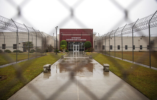 The Stewart Detention Center is seen through the front gate, Friday, Nov. 15, 2019, in Lumpkin, Ga. The rural town is about 140 miles southwest of Atlanta and next to the Georgia-Alabama state line. The town's 1,172 residents are outnumbered by the roughly 1,650 male detainees that U.S. Immigration and Customs Enforcement said were being held in the detention center in late November. (AP Photo/David Goldman)