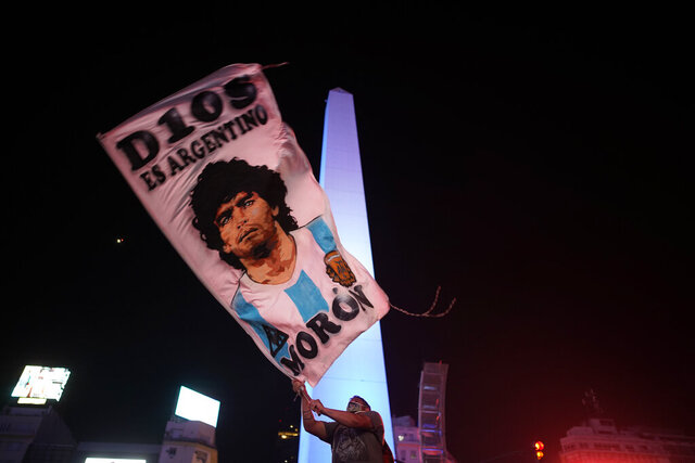 A man waves a flag with the image of Diego Maradona in downtown Buenos Aires, Argentina, Wednesday, Nov. 25, 2020. Maradona, the Argentine soccer great who was among the best players ever and who led his country to the 1986 World Cup title, died of a heart attack at his home in Buenos Aires. He was 60. (AP Photo/Victor Caivano)