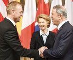 German minster of Defense Ursula von der Leyen, center, smiles when United States Secretary of Defense Patrick Shanahan, left, shakes hands with the Turkish minster of Defense Hulusi Akar, right, during the International Security Conference in Munich, Germany, Friday, Feb. 15, 2019. (Tobias Hase/dpa via AP)